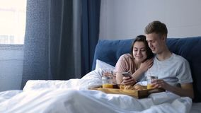 Joyful lovers having breakfast in bed at home stock video footage