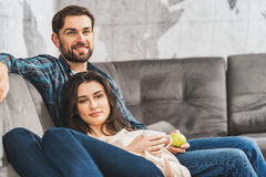 Joyful lovers spending time together. There is no place like home. Pretty young married couple is relaxing on sofa together. Man is holding apple and smiling royalty free stock images