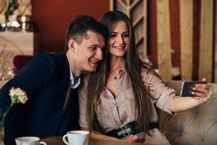 Joyful loving couple enjoying modern technology, having fun, capturing bright moments of vacations in cafe royalty free stock photo