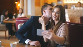 Joyful loving couple enjoying modern technology, having fun, capturing bright moments of vacations in cafe. Taking selfie on mobile phone camera stock video footage