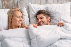Joyful loving couple waking up. Happy men and women are lying under warm quilt in bed. They are looking at each other with love and smiling Royalty Free Stock Photo
