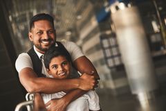 Joyful loving father embracing his little son. Overjoyed pleasant hindu men standing at the railway station while embracing his beloved smiling son royalty free stock images