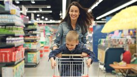 Joyful loving mother is having fun in supermarket with her cute little son, she is running with shopping cart with small stock video