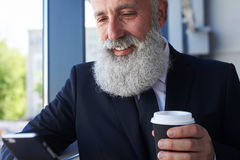 Joyful male age of 50-60 holding cup of coffee and surfing in ph Royalty Free Stock Photography