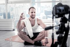 Joyful male blogger giving advice about proteins. Additional vitamins. Gay handsome male blogger preparing materials for blog while posing on mat board and royalty free stock image
