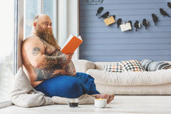 Joyful male fatso reading at home Stock Photography