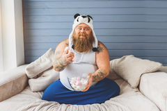 Joyful male glutton prefers unhealthy eating. I want more zephyrs. Happy fat man is holding sweet food in his hand with joy. He is sitting on sofa and smiling stock image