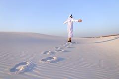 Joyful male Muslim walks through white sand desert and enjoys li Stock Photos