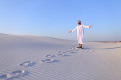 Joyful male Muslim walks through white sand desert and enjoys li Stock Images