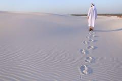 Joyful male Muslim walks through white sand desert and enjoys li Stock Image