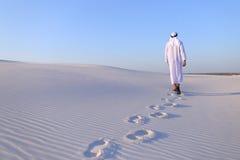 Joyful male Muslim walks through white sand desert and enjoys li Royalty Free Stock Image