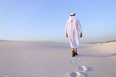 Joyful male Muslim walks through white sand desert and enjoys li Stock Photo