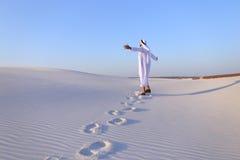 Joyful male Muslim walks through white sand desert and enjoys li Royalty Free Stock Photography