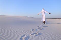Joyful male Muslim walks through white sand desert and enjoys li Stock Photography