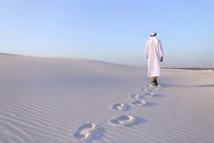 Joyful male Muslim walks through white sand desert and enjoys li Royalty Free Stock Images