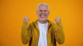 Joyful male pensioner showing success gesture and smiling on camera satisfaction stock video