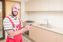 Joyful male plumber texting in the kitchen. On his mobile phone after finishing his work with copy space area Royalty Free Stock Photos
