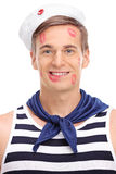 Joyful male sailor covered in lipstick kiss marks. Vertical shot of a joyful male sailor covered in lipstick kiss marks looking at the camera and smiling Royalty Free Stock Photos