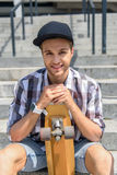 Joyful male skateboarder resting on steps. Cute young guy is holding his skate and smiling. He is sitting on stairs and relaxing Stock Images