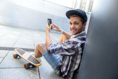 Joyful male skater entertaining with smartphone. Happy young man is sitting and using mobile phone. He is looking at camera and smiling. Skateboard near him Royalty Free Stock Photos