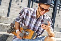 Joyful male skater using smartphone on steps. Carefree young man is listening to music from earphones. He is holding mobile phone and laughing. Guy is sitting on Royalty Free Stock Photo