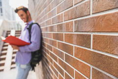 Joyful male student learning lesson outdoors. Carefree young man is reading textbook with interest. He is standing near building and smiling. Focus on wall Royalty Free Stock Image