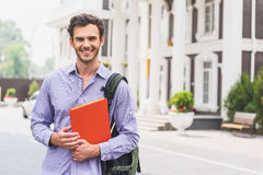 Joyful male student posing with book. I prefer studying. Happy young man is holding textbook and laughing. He is standing near university Stock Images