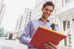 Joyful male student studying in city. Happy young man is reading document from folder. He is standing on street and smiling Stock Photos