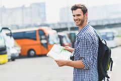 Joyful male tourist is ready to travel. I like traveling. Happy young man is standing on bus station and holding map. He is looking at camera and smiling Royalty Free Stock Photography