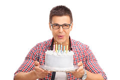 Joyful man blowing candles on a birthday cake Royalty Free Stock Photo