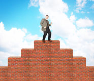 Joyful man climbed on the brick pyramid Royalty Free Stock Photo