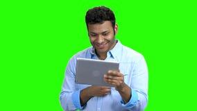 Joyful man with digital tablet on green screen. stock video