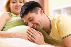 Joyful man embraces tummy of his pregnant wife Stock Images