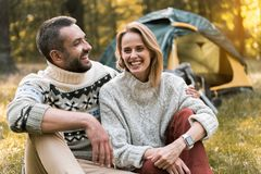 Joyful man embracing woman with love outdoors. Portrait of happy married couple hugging while relaxing in the nature. They are sitting on grass and smiling Royalty Free Stock Photos