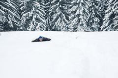 Joyful man gets out of a snow cave in the winter forest Royalty Free Stock Image