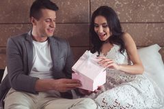 Free Joyful Man Giving Present To Fiancee In Hotel Bedroom Stock Photography - 119185352