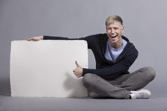Joyful man giving thumbs up at empty signboard. Royalty Free Stock Photos