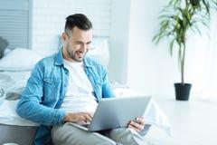 Joyful man grinning broadly while using laptop Stock Images