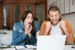 Joyful man happily yes gesture while girl sitting near and amazedly looking on laptop. Young people using laptop for royalty free stock image