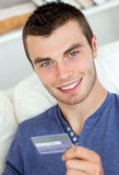 Joyful man holding a card smiling at the camera Royalty Free Stock Photos