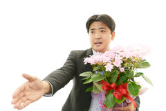 Joyful man holding flower bouquet Stock Images