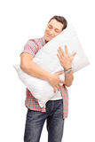 Joyful man hugging a pillow with his eyes closed Royalty Free Stock Photography
