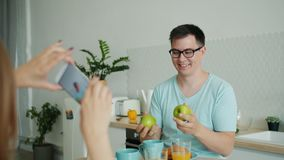 Joyful man juggling fruit in kitchen while wife taking photo with smartphone. Joyful handsome man is juggling fruit in kitchen while wife is taking photo with stock video
