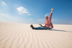 Joyful man with a laptop sits in desert Royalty Free Stock Images