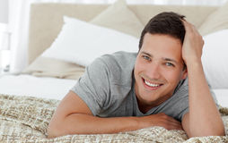 Joyful man lying on th edge of his bed at home. And looking at the camera Royalty Free Stock Photography