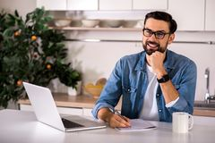 Joyful man making notes in the kitchen stock photo