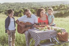 Joyful man performing son on guitar for family. Happy family are having fun on picnic in the nature. Father is playing guitar while his son listening to music stock photography