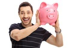 Joyful man with a piggybank Stock Image