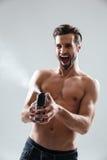 Joyful man playing with deodorant Stock Images