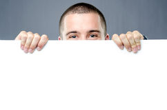 Joyful man protrudes behind white board Royalty Free Stock Image